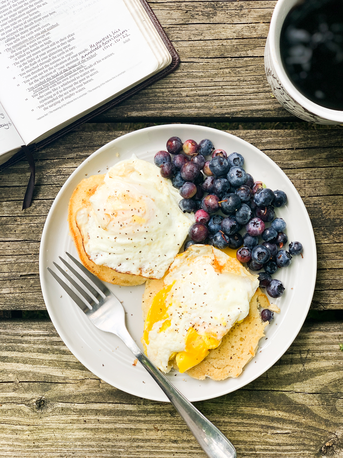leftover pancakes with fried eggs and blueberries on a picnic table