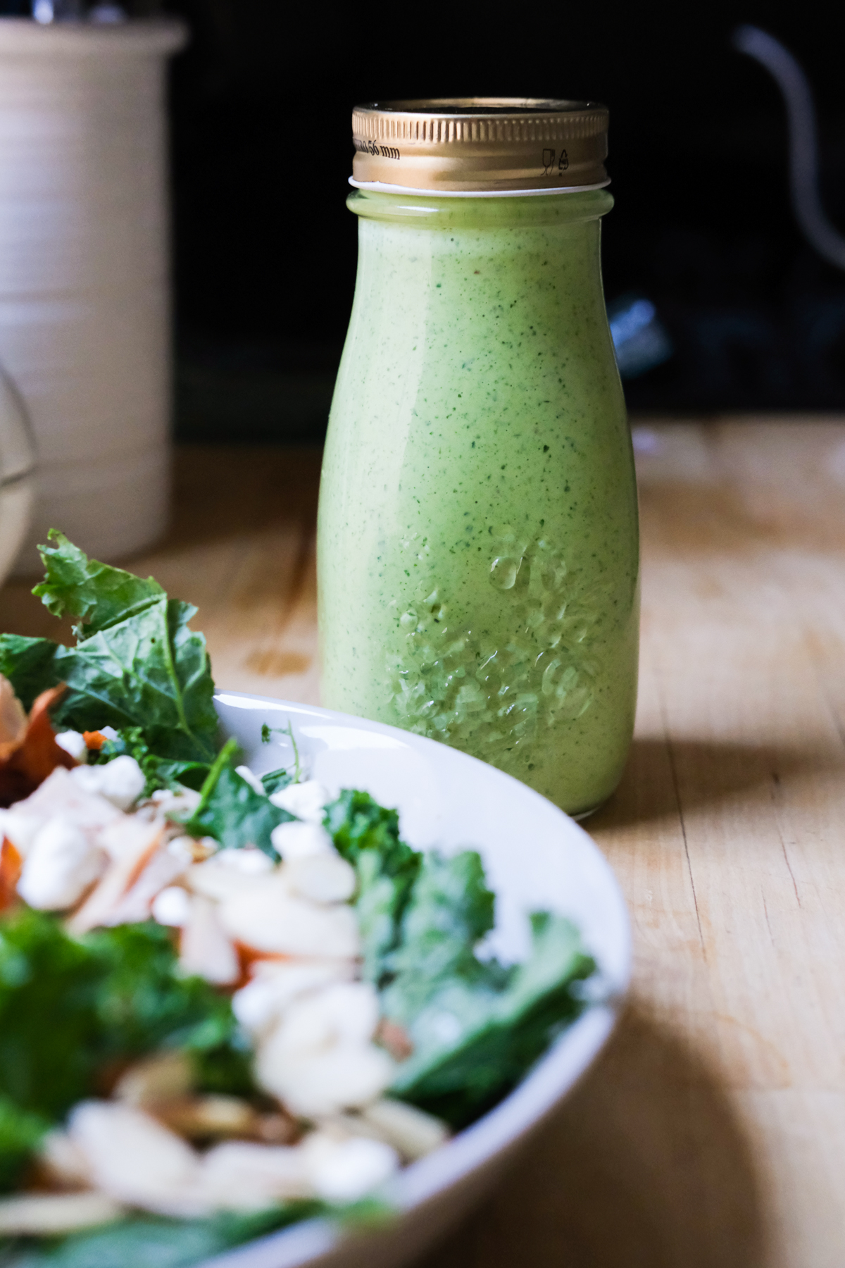 green goddess dressing in a bottle next to salad