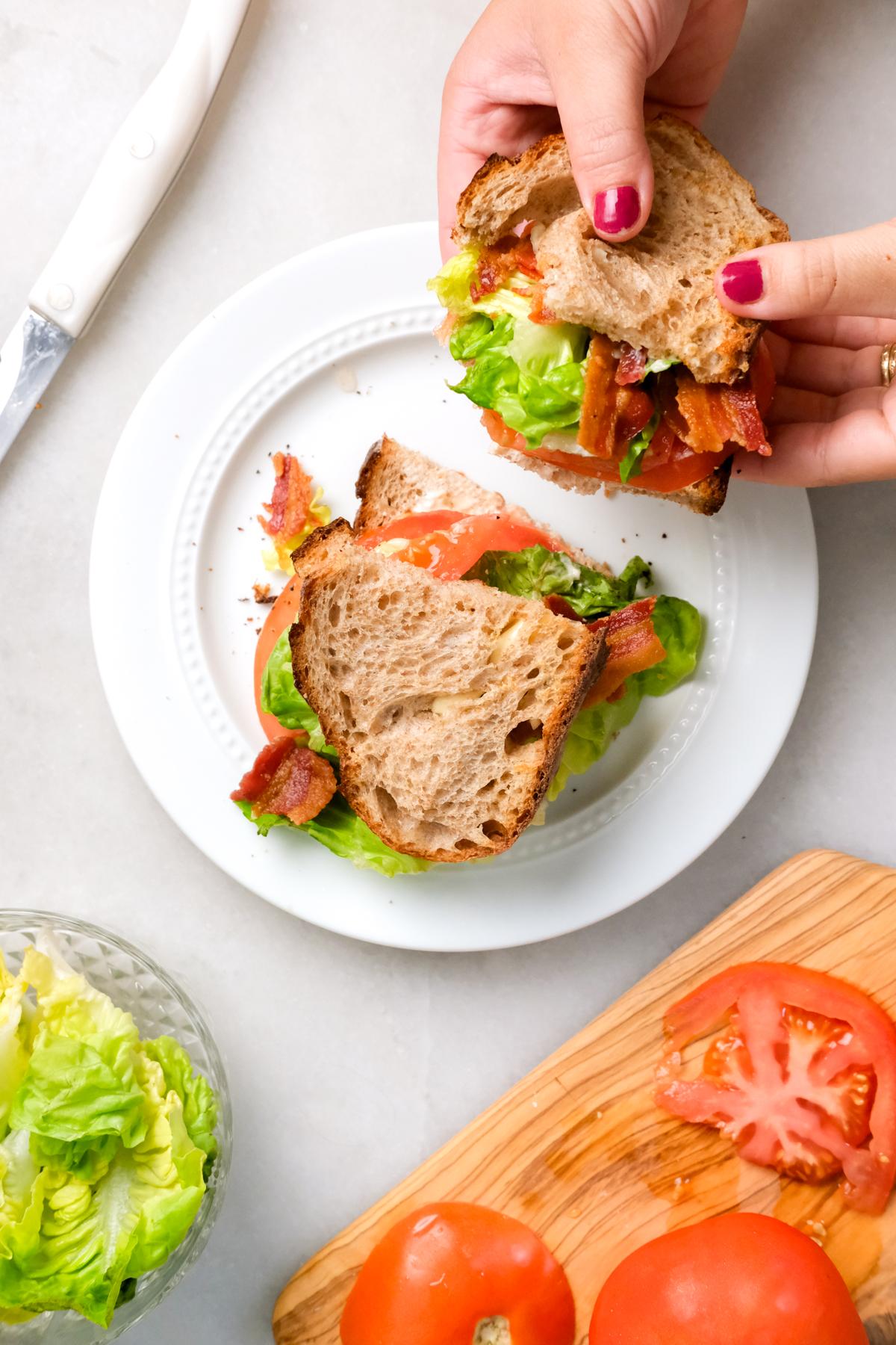 grabbing half of a BLT sandwich off a plate