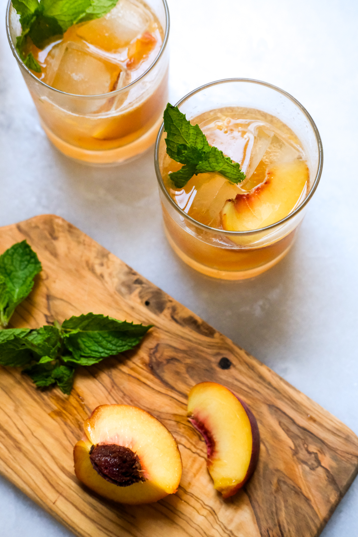 peach bourbon smash cocktails with peach slices and mint garnish