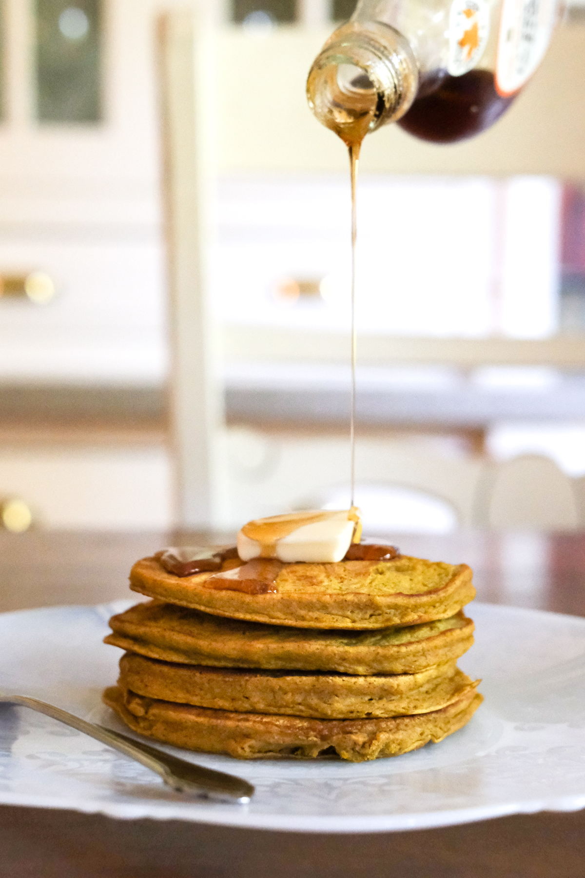 pouring syrup on a stack of pumpkin pancakes
