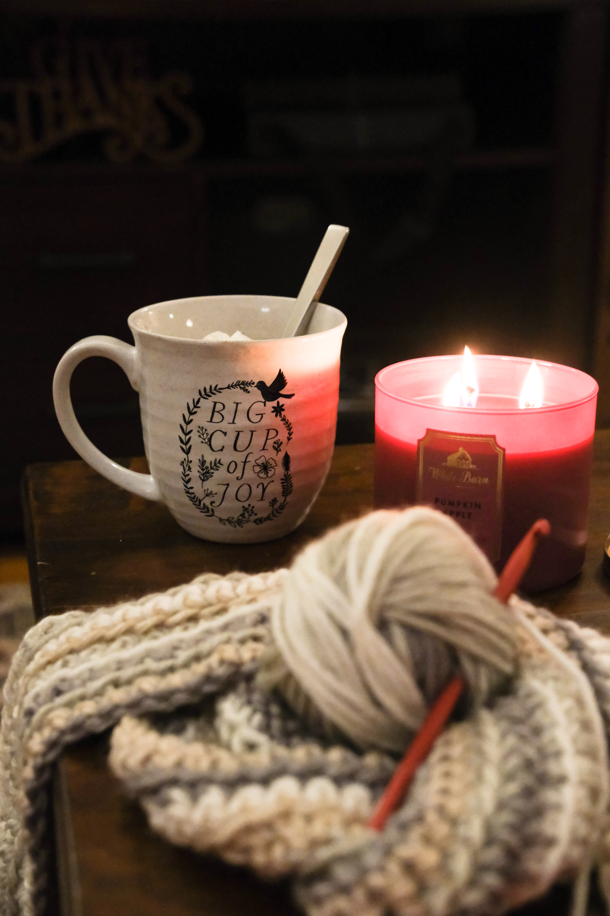 mug candle and crochet project on a coffee table