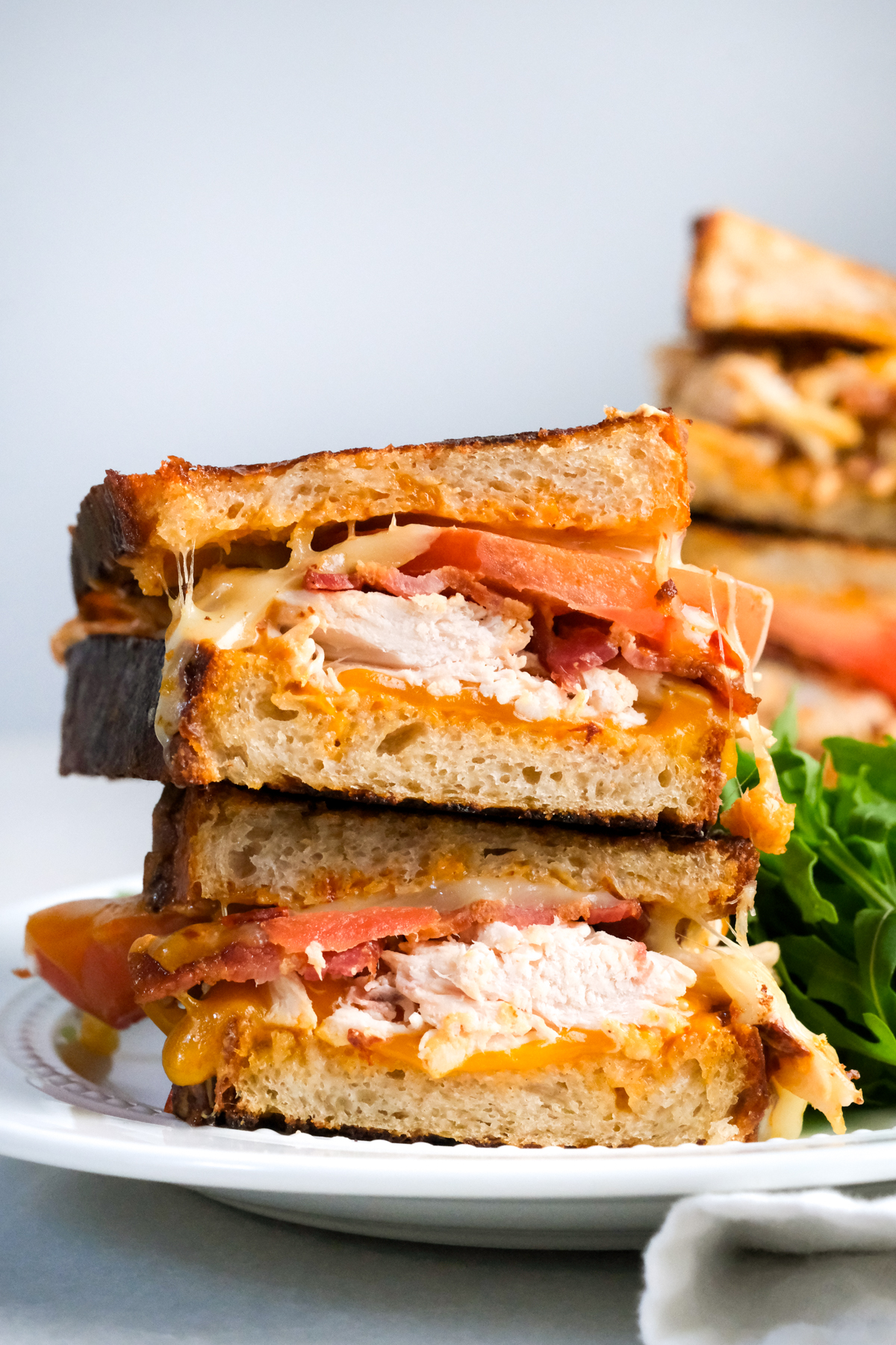 halves of a chipotle chicken bacon toastie stacked on top of each other