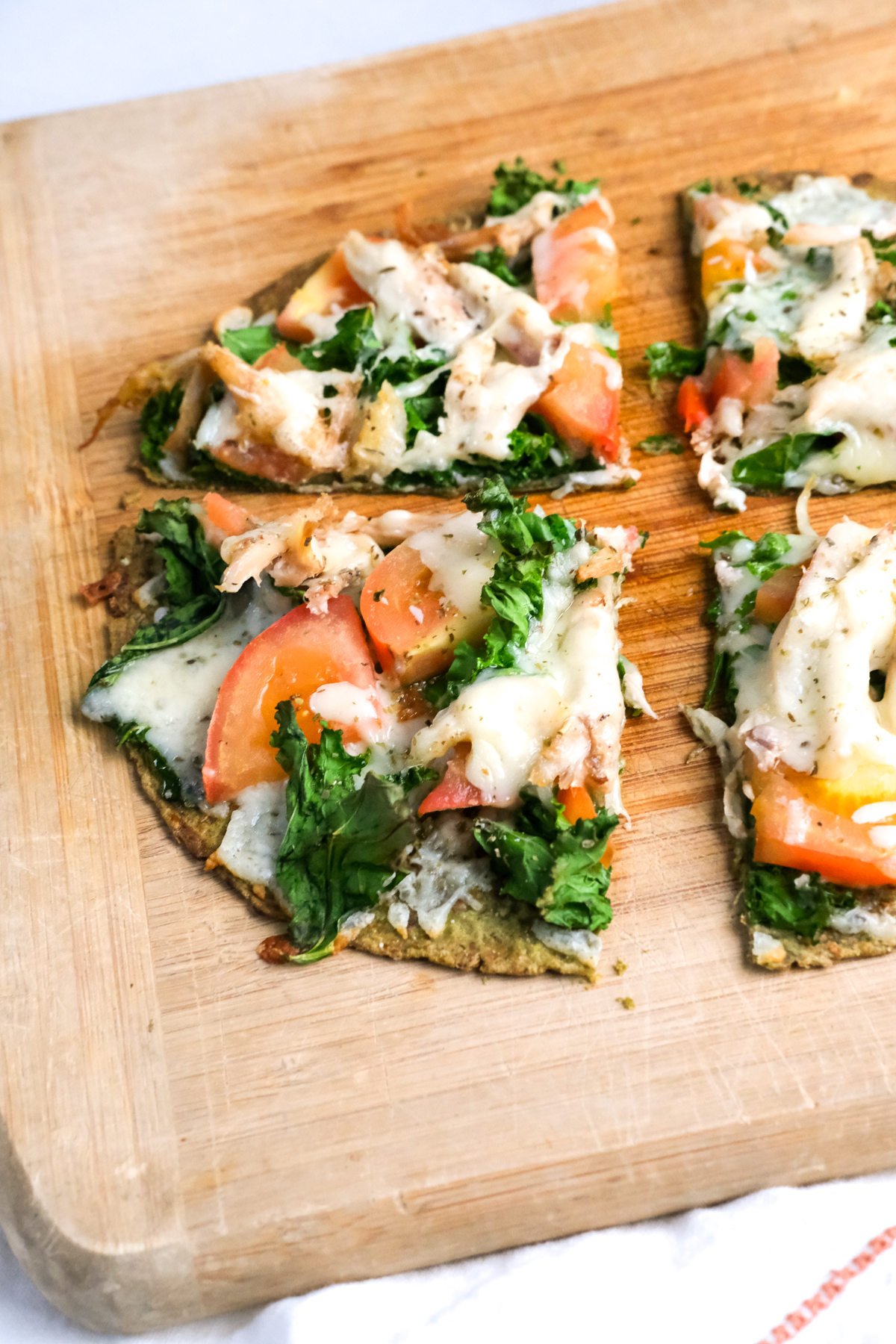 chicken flatbread on a wooden cutting board