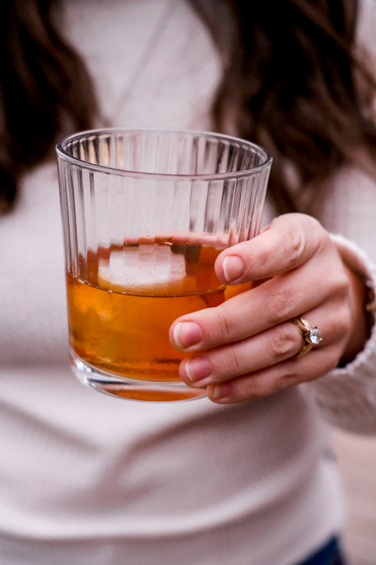 holding a classic old fashioned cocktail