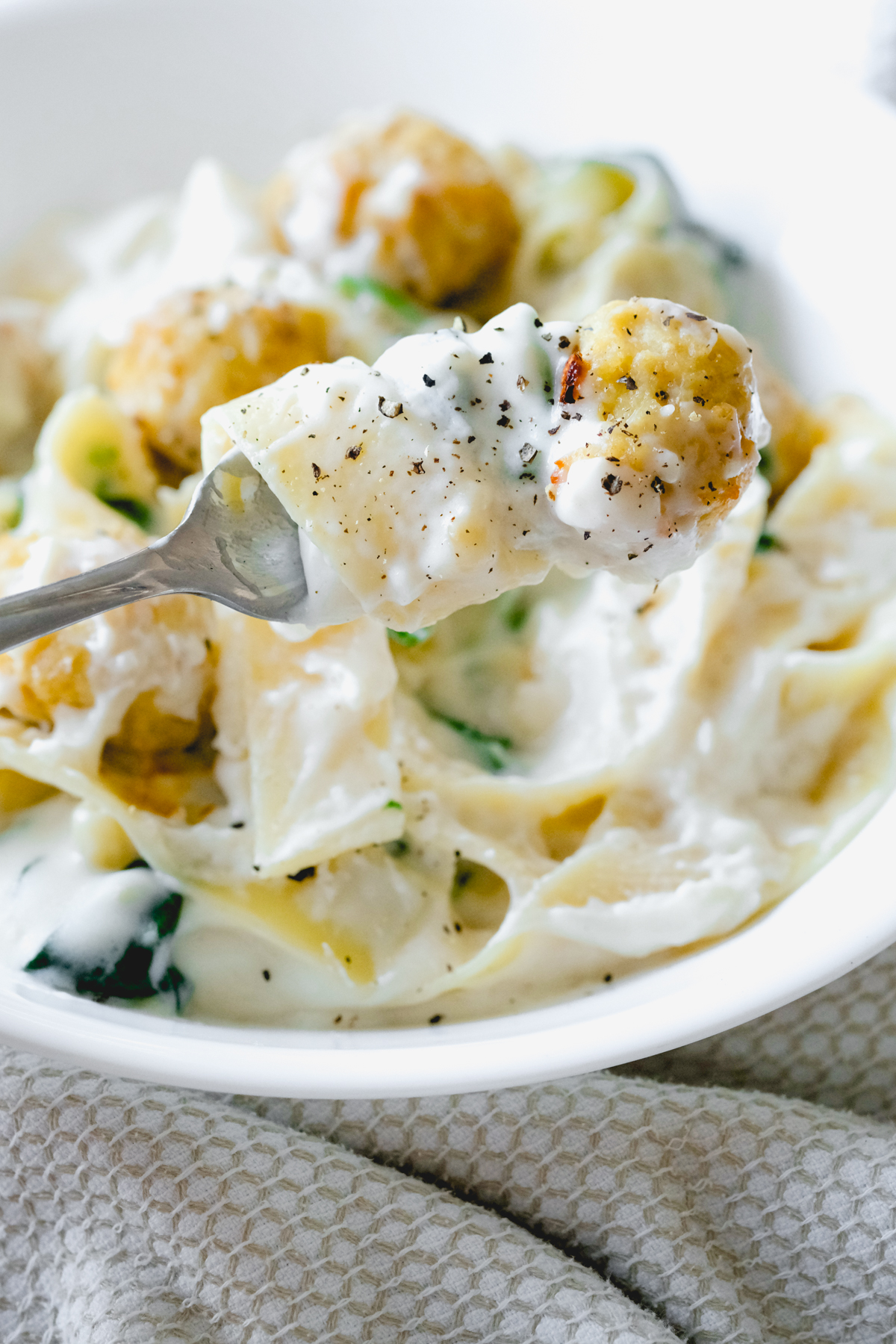 chicken meatball with cheesy spinach pappardelle on a fork