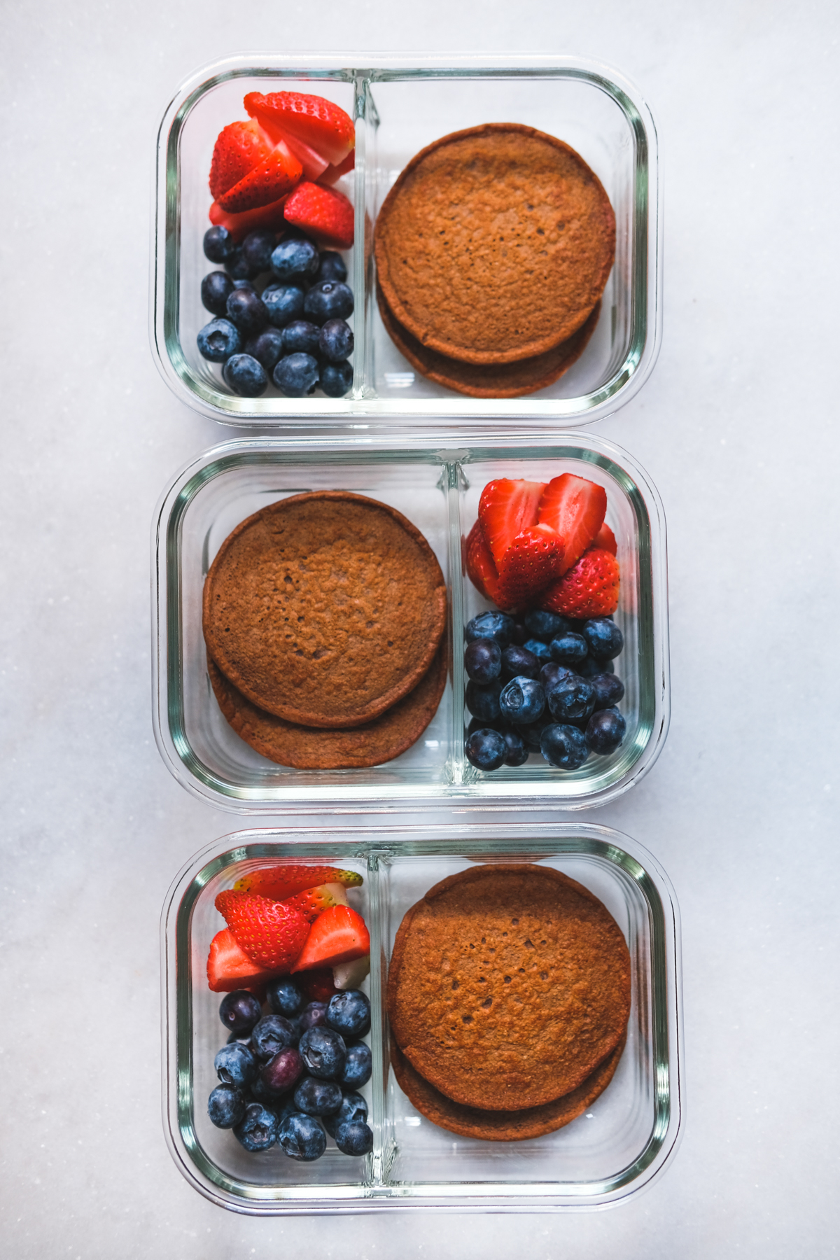 chocolate protein pancakes in meal prep containers with berries