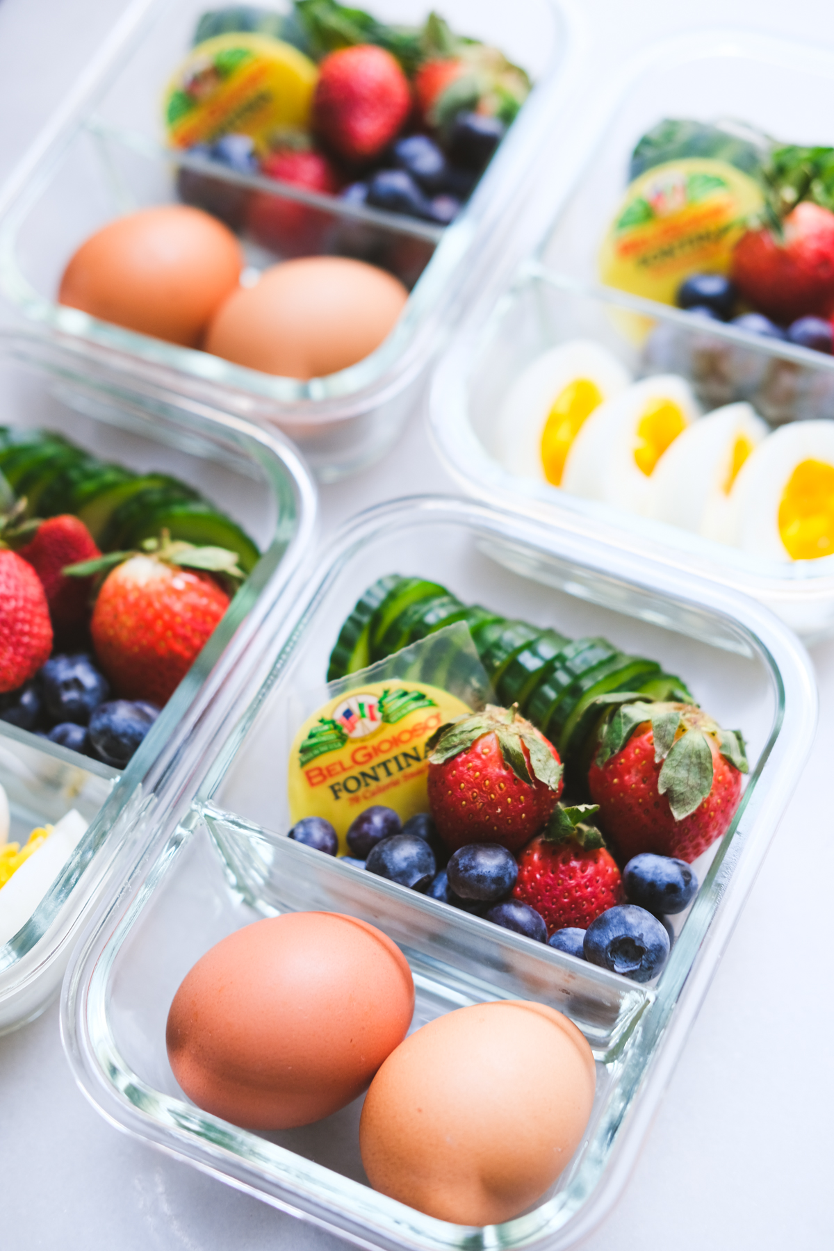 meal prep containers with veggies fruit cheese and eggs