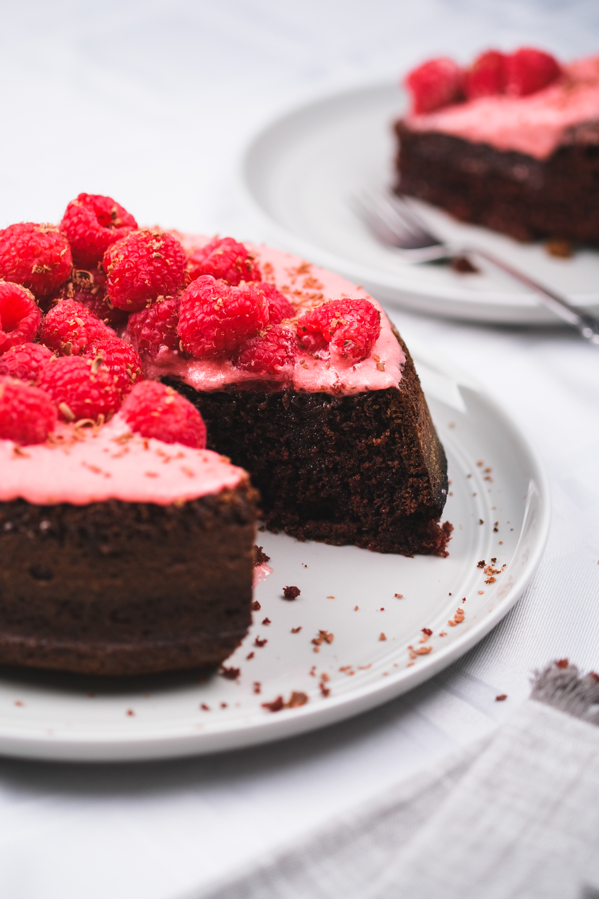 slicing up a chocolate raspberry cake with fresh berries and chocolate shavings
