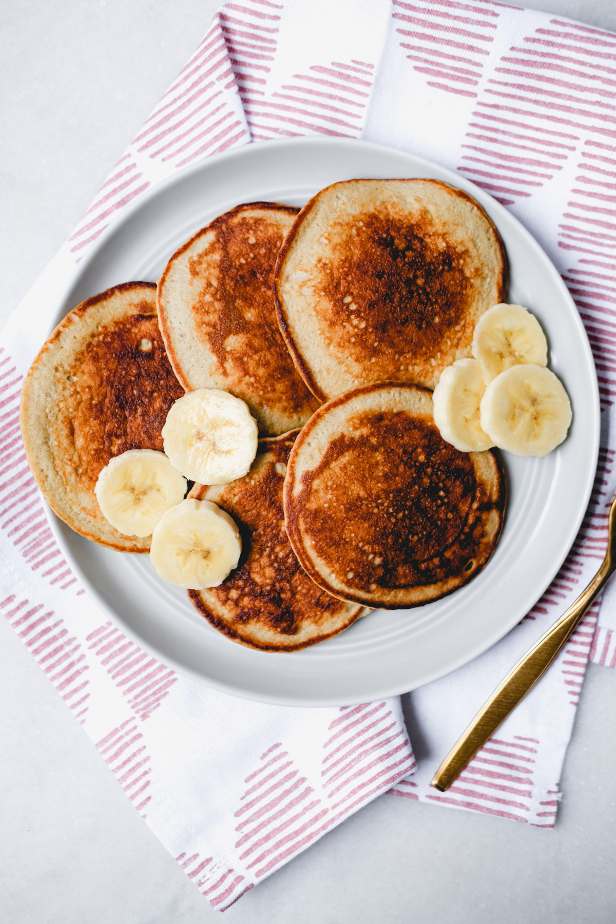 banana oatmeal pancakes with banana slices on a grey plate