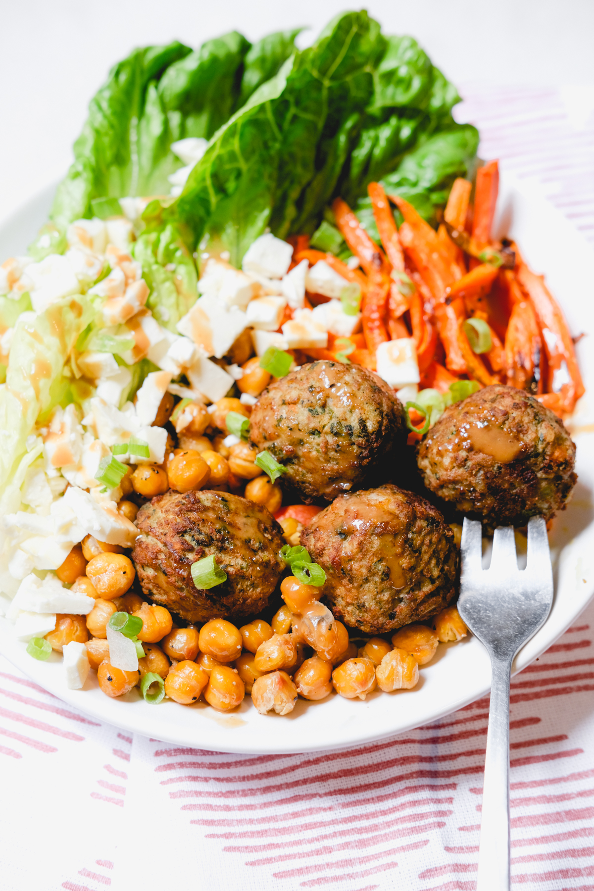 meatball and chickpeas in a salad with carrots, lettuce, and feta cheese