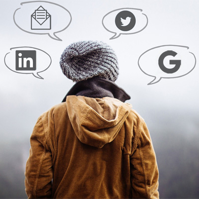 A woman in a tan coat and grey hat thinking about social media marketing services