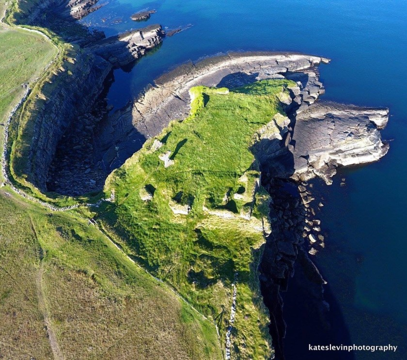 An aerial view of the ruins of Kilbarron Castle perched at the top of the cliffs of the promontory jutting out into Donegal Bay.