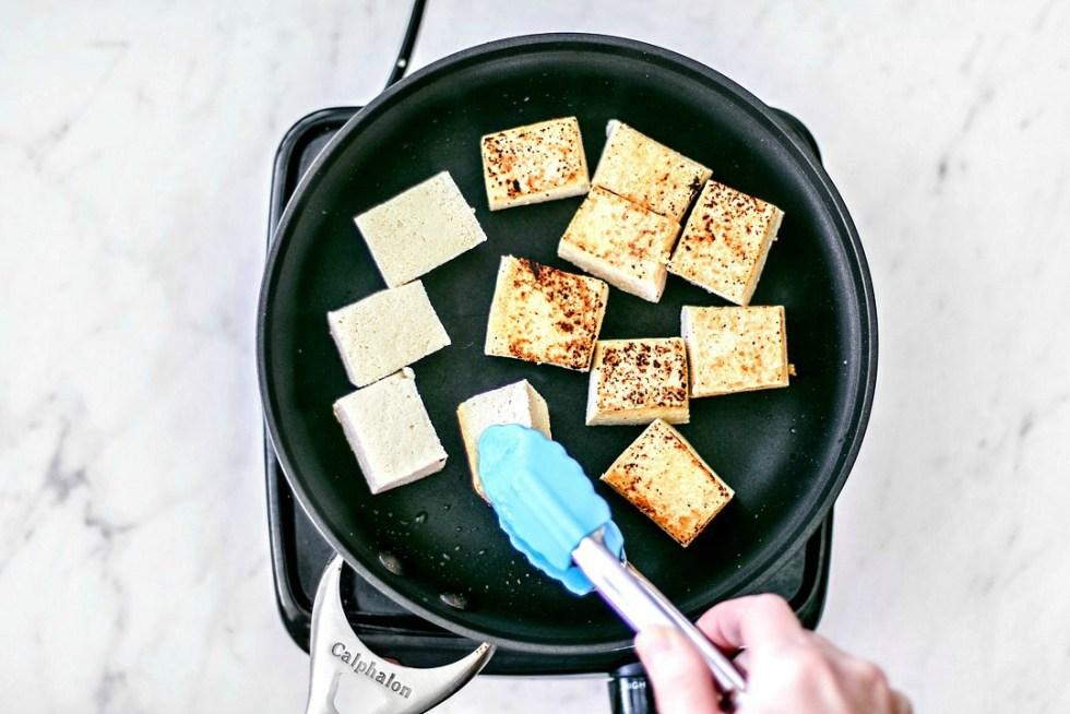 Tofu being pan-fried to a crisp.