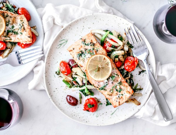 Plates of grilled salmon over salad.