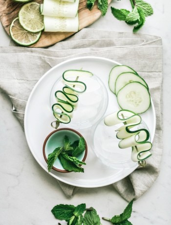 Glasses of cucumber mint gin fizz with ingredients sprawled around them.