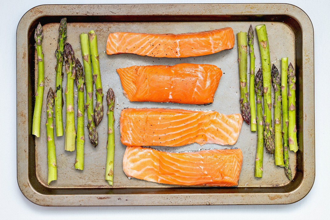 Raw salmon on a baking sheet with asparagus