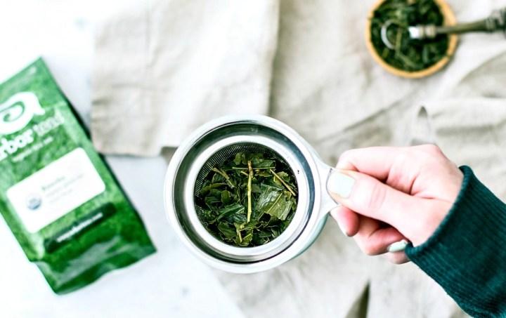 Green tea leaves in infuser