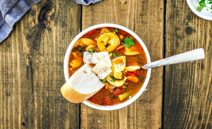 Bowl of vegetable and tortellini soup with bread.