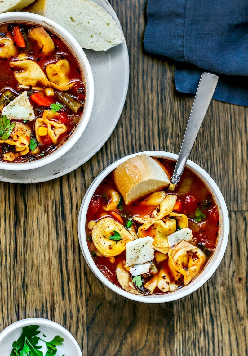 Two bowls of vegetable soup with cheese tortellinis.