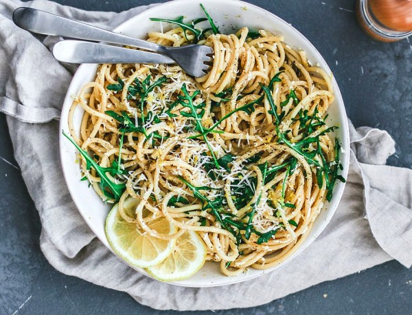 Pasta al Limone piled in a bowl with arugula, whirled around a fork.