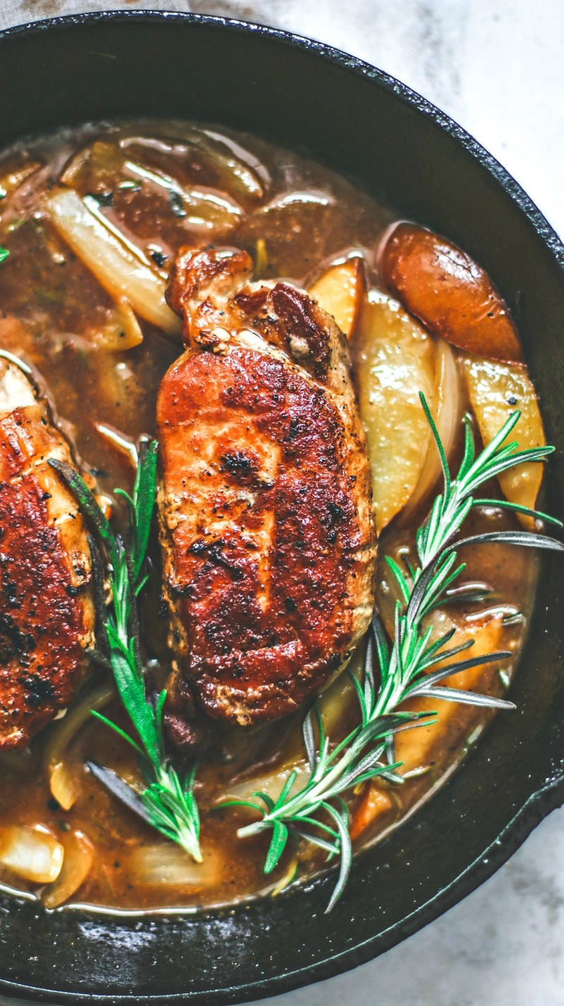 Close up of browned pork chops in a skiller with rosemary and pear and ginger sauce.