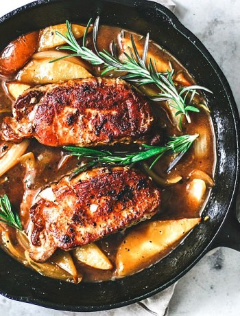 Browned pork chops in a skiller with rosemary and pear and ginger sauce.