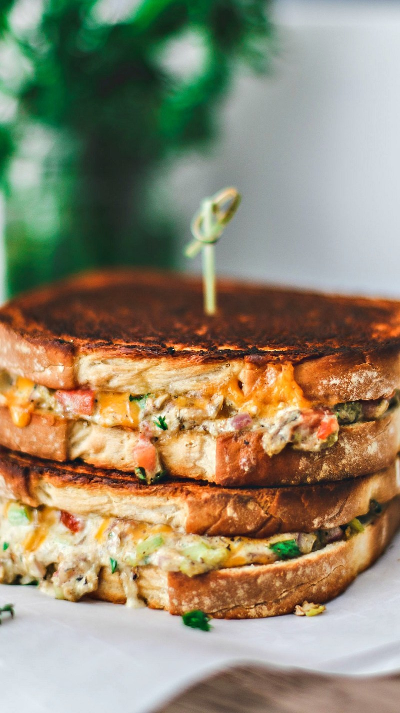 Close up of Cheddar Jalapeño Gourmet Grilled Cheese sandwiches stacked on top of one another in a melted mess.