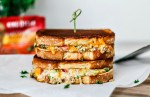 Cheddar Jalapeño Gourmet Grilled Cheese sandwiches stacked on top of one another in a melted mess.