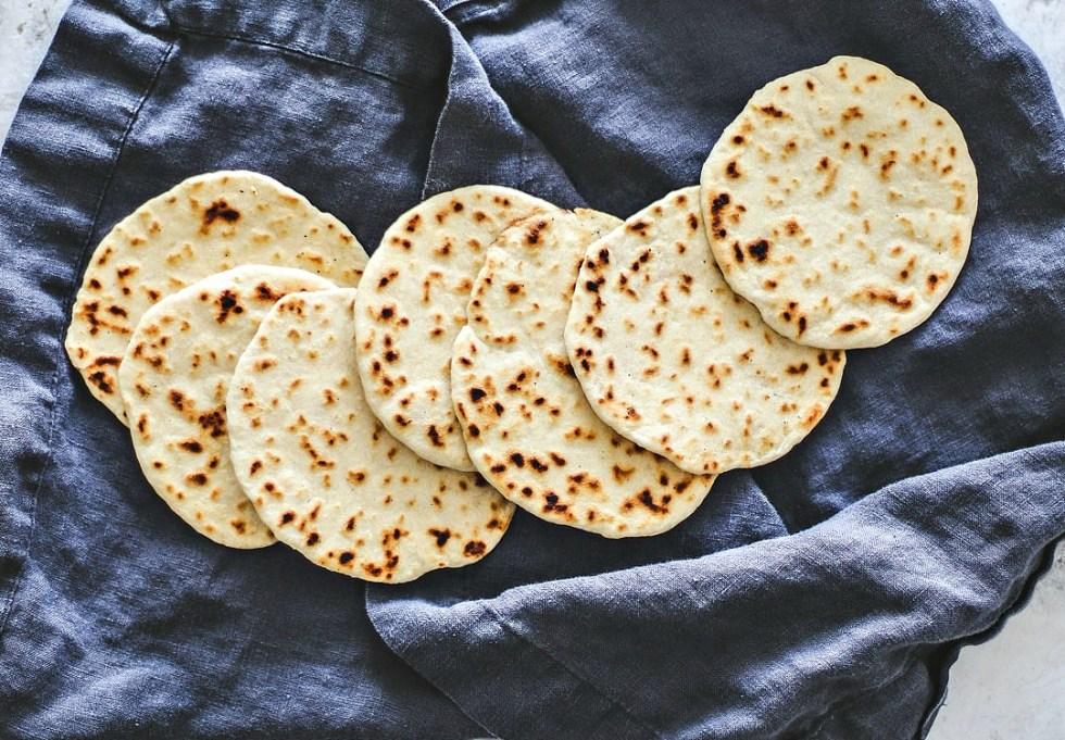 Homemade flour tortillas spread out over cloth.