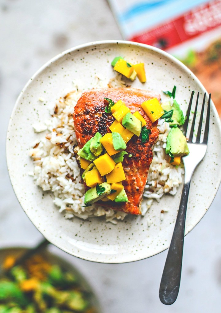 Close up of pan-seared salmon on plate over rice and topped with mango and avocado salsa.