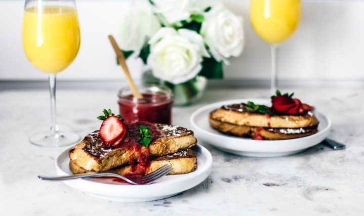 Pretty springtime table setting with stacks of french toast and mimosas.