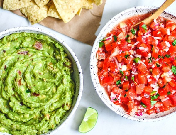 Bowls full of salsa and guacamole with a handful of chips.