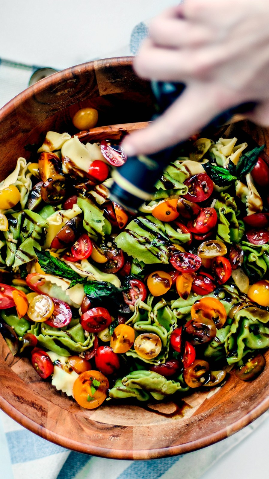 Bruschetta pasta salad being drizzled with balsamic glaze.