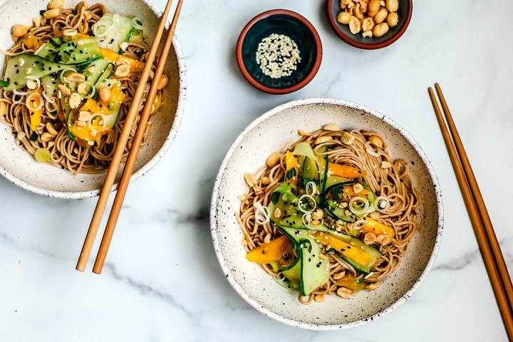 Bowls of sesame noodles with cucumber and mango salad.