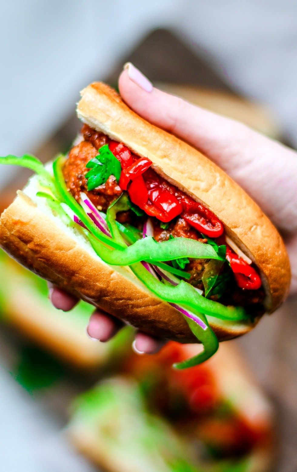 Hand holding up loaded meatball sub.