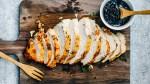 Roast turkey sliced on a wooden cutting board.