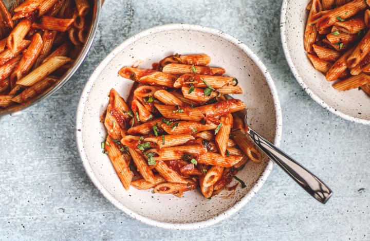 Bowl of penne tossed in marinara.