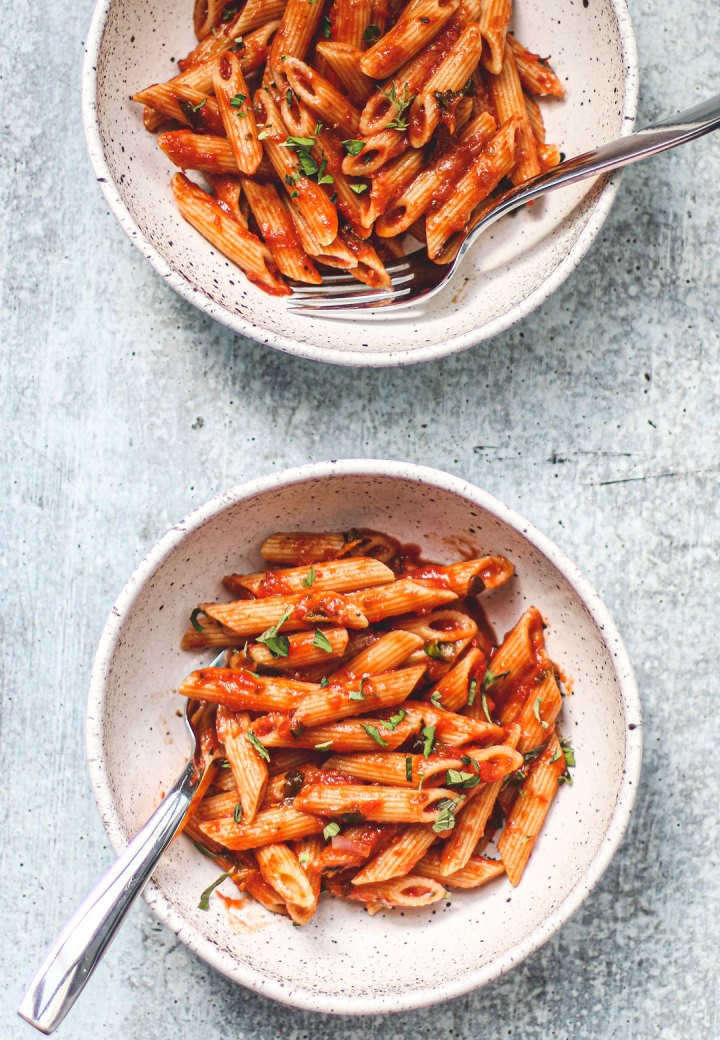Two bowls of penne tossed in marinara.