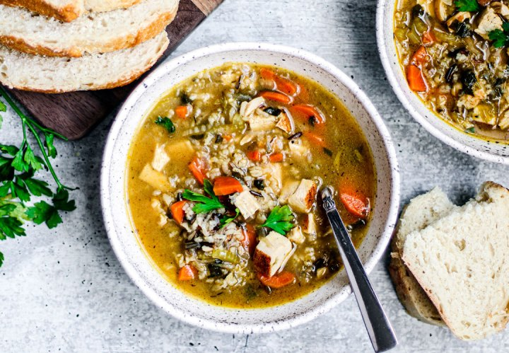 A bowl of turkey and wild rice soup with slices of fresh bread.