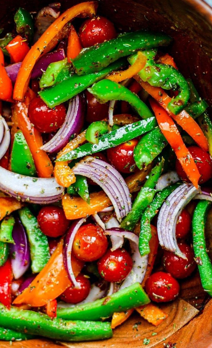 Bowl full of fresh seasoned vegetables.