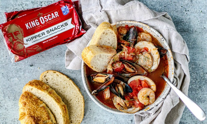 Bowl of cioppino with fresh bread and King Oscar Kipper Snacks packaging.