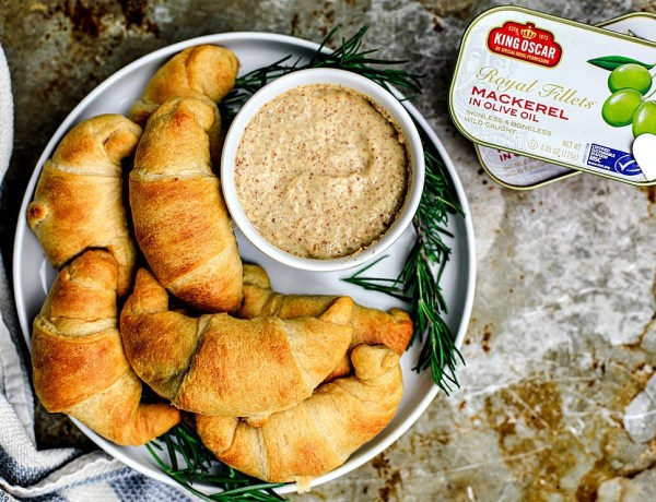 Plate of cheesy crescent rolls with can of King Oscar Mackerel next to it.