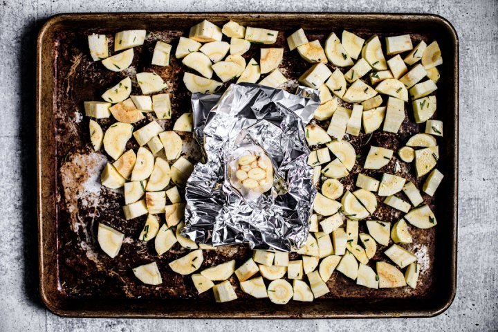 Sheet pan full of cubed parsnips and a head of garlic in tinfoil.