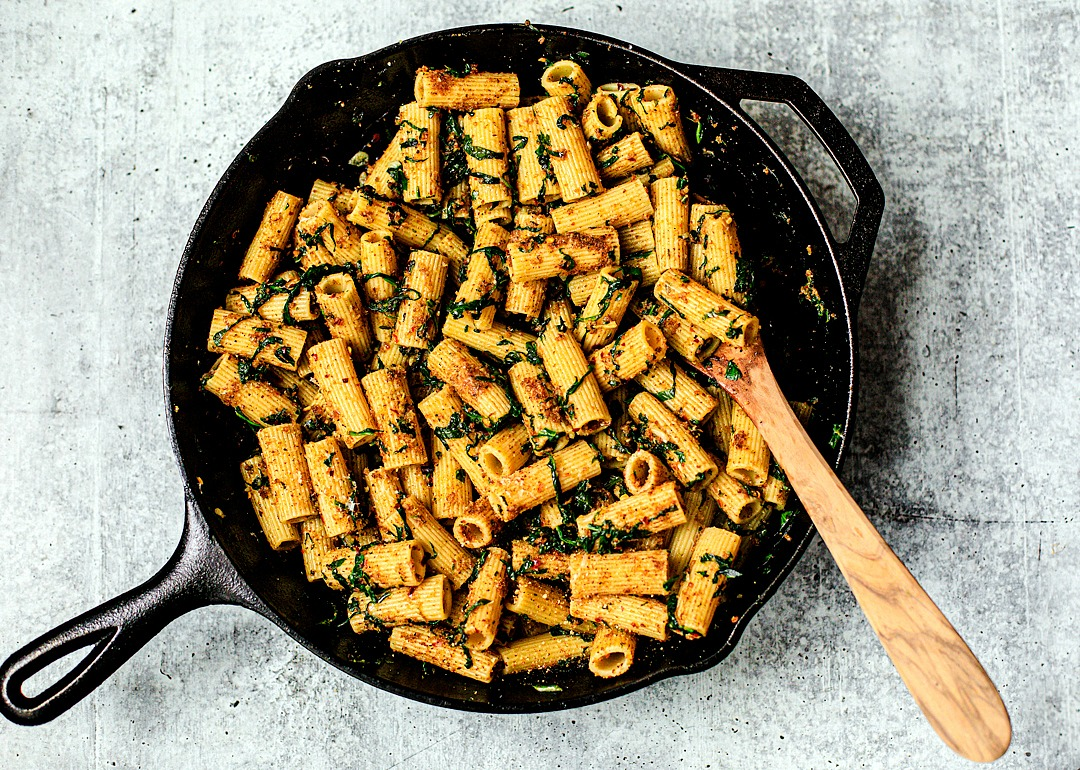 Skillet full of rigatoni pasta mixed in with garlid, spinach, and breadcrumbs.