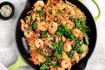 Skillet full of Ramen noodles, shrimp, and vegetables.