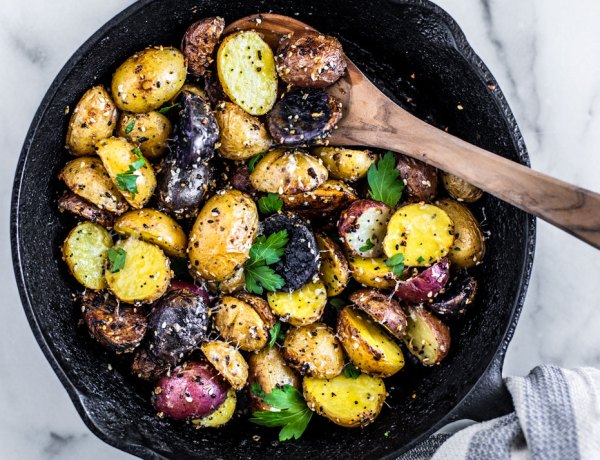 Cast iron skillet full of everything bagel seasoned roasted potatoes with fresh herbs on top.