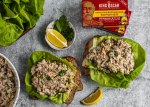 Slices of toasted bread topped with bibb lettuce and sardine salad.