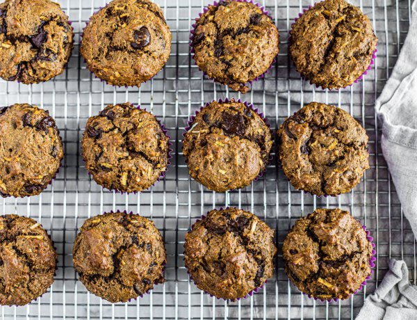 Whole wheat chocolate chip muffins lined up on a cooling rack.