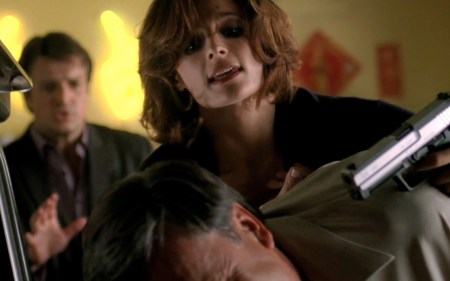 Stana Katic as Kate Becket, inpsiration for Nikki Heat, holding russian mobster at gunpoint